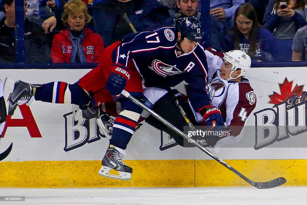 Brandon Dubinsky of the Columbus Blue Jackets checks Tyson Barrie of the Colorado Avalanche while chasing after the puck during the first period on...