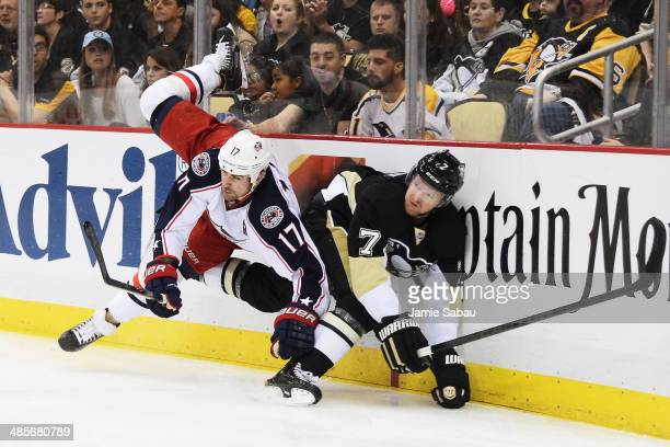 Brandon Dubinsky of the Columbus Blue Jackets finishes a check on Paul Martin of the Pittsburgh Penguins in the first period in Game Two of the First...