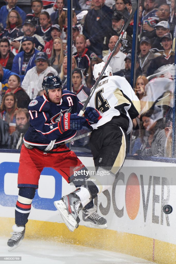 Brandon Dubinsky of the Columbus Blue Jackets follows the loose puck after colliding with Rob Scuderi of the Pittsburgh Penguins during the first...
