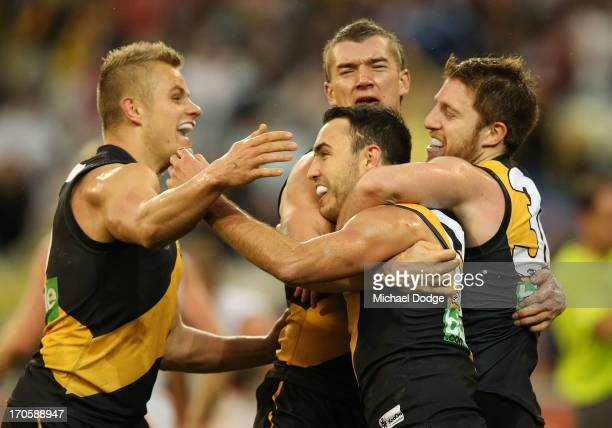 Brandon Ellis Dustin Martin and Reece Conca of the Tigers hug Shane Edwards after he kicked a goal during the round 12 AFL match between the Richmond...