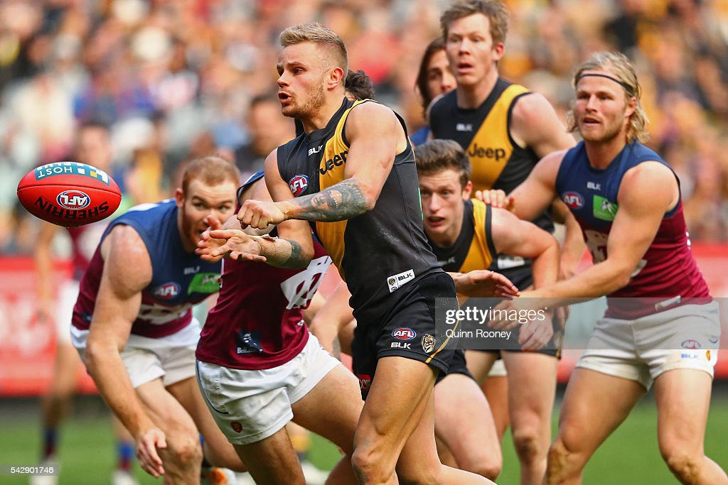 Brandon Ellis of the Tigers handballs during the round 14 AFL match between the Richmond Tigers and the Brisbane Lions at Melbourne Cricket Ground on June 25, 2016 in Melbourne, Australia.