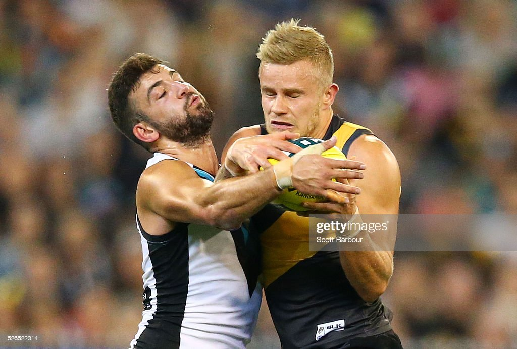 Brandon Ellis of the Tigers is tackled by Jimmy Toumpas of the Power during the round six AFL match between the Richmond Tigers and the Port Adelaide Power at Melbourne Cricket Ground on April 30, 2016 in Melbourne, Australia.