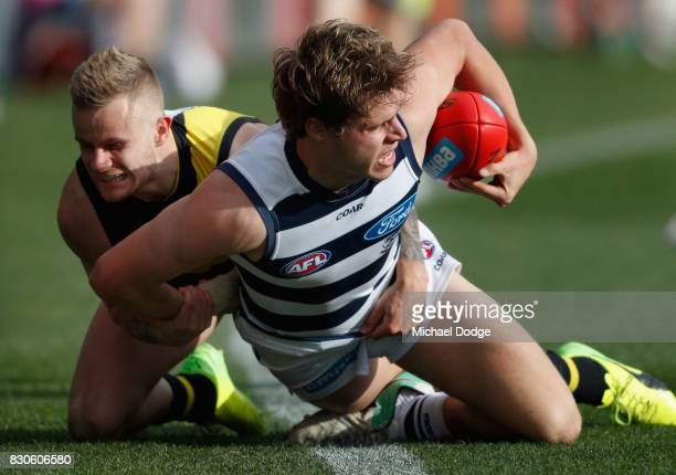 Brandon Ellis of the Tigers tackles Jake Kolodjashnij of the Cats during the round 21 AFL match between the Geelong Cats and the Richmond Tigers at...