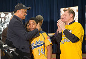 Brandon Green a catcher and pitcher for the Jackie Robinson West Little League baseball team is embraced by civil rights leader Rev Jesse Jackson...
