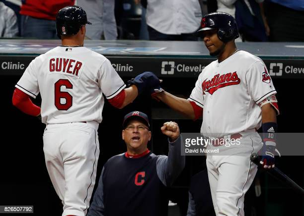 Brandon Guyer of the Cleveland Indians is congratulated by Edwin Encarnacion and Manager Terry Francona after scoring in the fifth inning against the...
