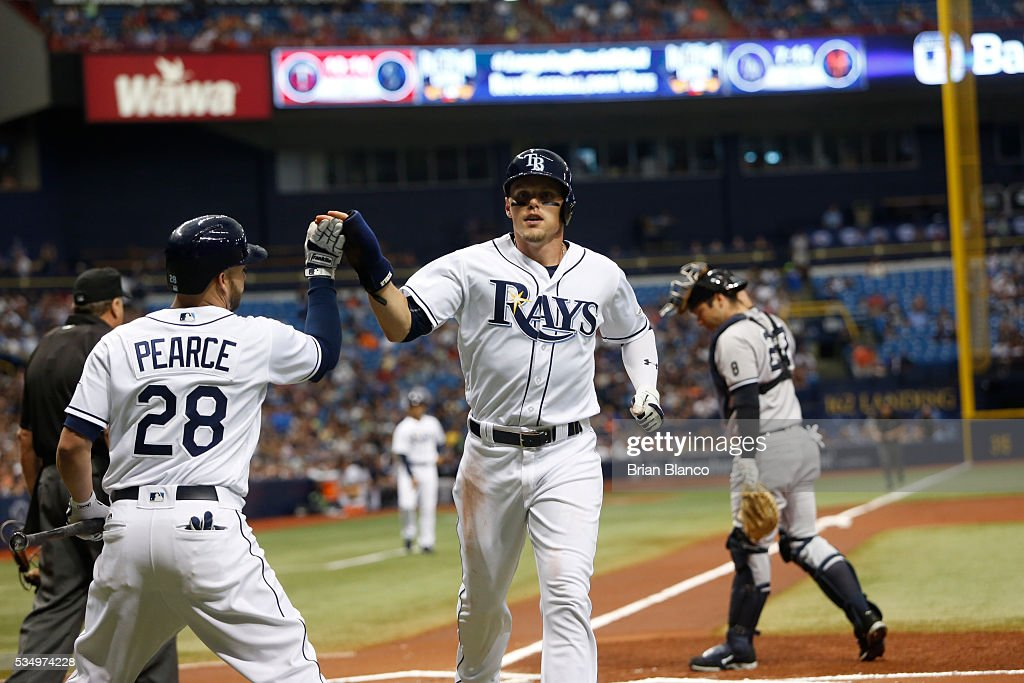 Brandon Guyer #5 of the Tampa Bay Rays celebrates with teammate Steve Pearce #28 after scoring off of a sacrifice fly by Evan Longoria during the first inning of a game against the New York Yankees on May 28, 2016 at Tropicana Field in St. Petersburg, Florida.