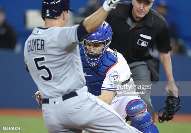 Brandon Guyer of the Tampa Bay Rays is tagged out at home plate in the eighth inning during MLB game as Josh Thole of the Toronto Blue Jays prepares...