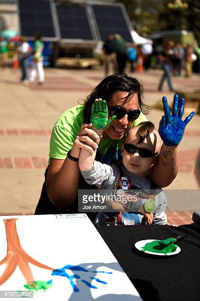 Brandon Harper 4 and his mom Nicholette of Thornton pose for a picture after adding their hand prints to the earth tree art work being made by Denver...