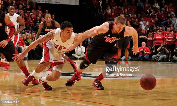 Brandon Harris of the Western Kentucky Hilltoppers and Stephan Van Treese of the Louisville Cardinals dive for a loose ball at Bridgestone Arena on...