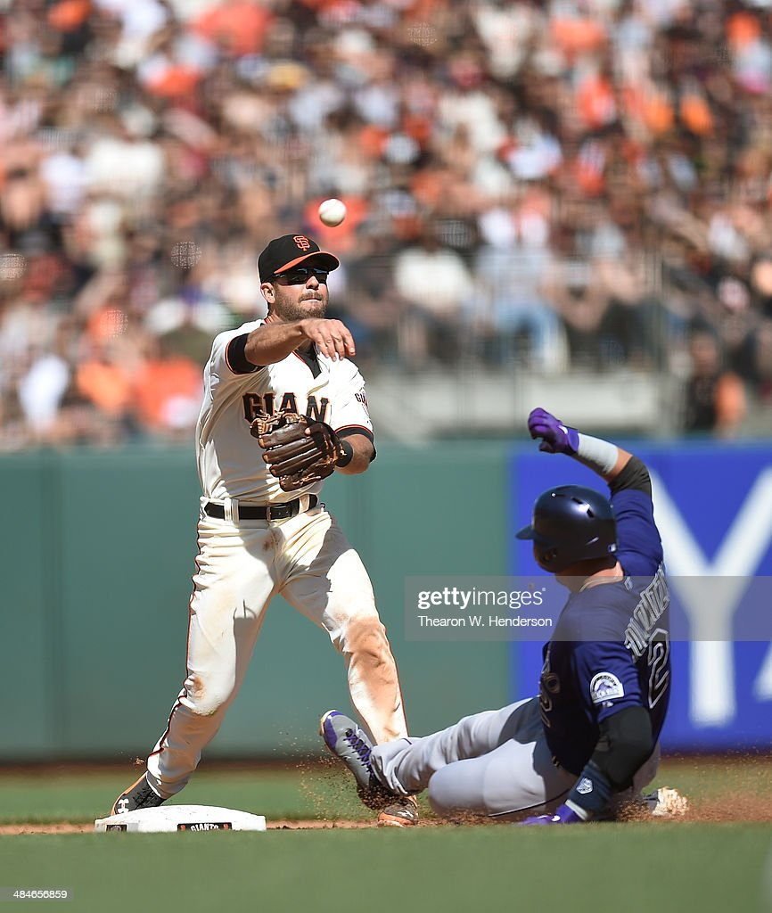 Brandon Hicks #14 of the San Francisco Giants completes the double-play getting his throw off over the top of Troy Tulowitzki #2 of the Colorado Rockies in the top of the ninth inning at AT&T Park on April 13, 2014 in San Francisco, California.