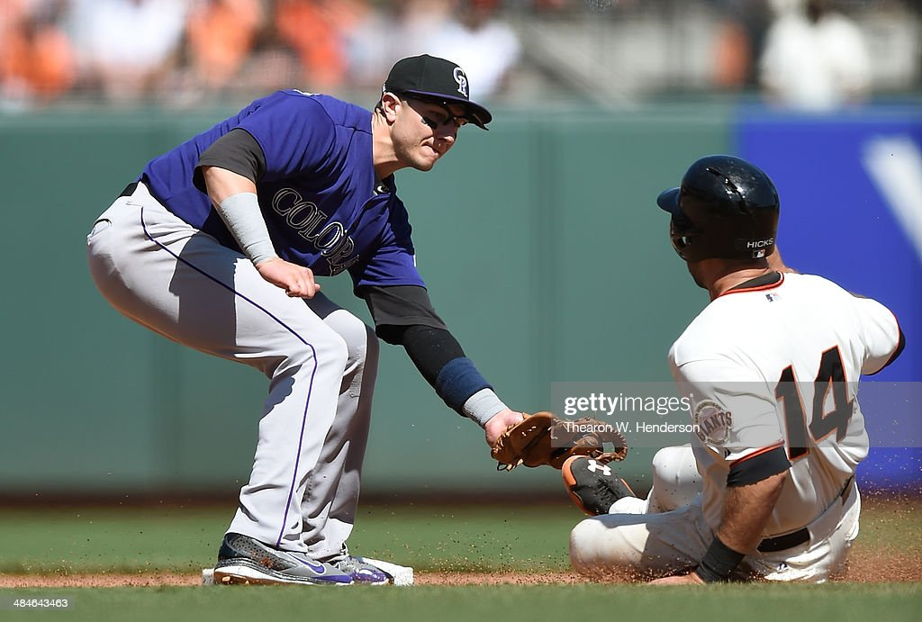 Brandon Hicks #14 of the San Francisco Giants tagged out stealing by Troy Tulowitzki #2 of the Colorado Rockies in the bottom of the seventh inning at AT&T Park on April 13, 2014 in San Francisco, California.