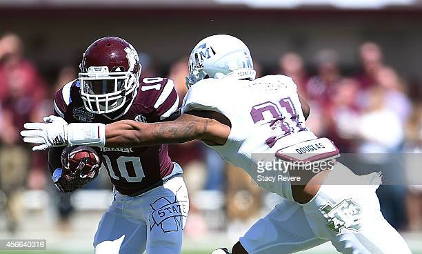 Brandon Holloway of the Mississippi State Bulldogs is pursued by Howard Matthews of the Texas AM Aggies during the second quarter of a game at Davis...