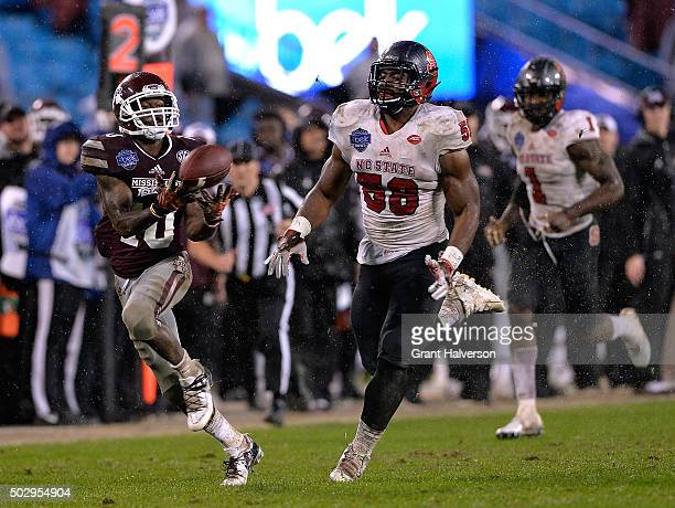 Brandon Holloway of the Mississippi State Bulldogs makes a touchdown catch against Airius Moore of the North Carolina State Wolfpack during the Belk...