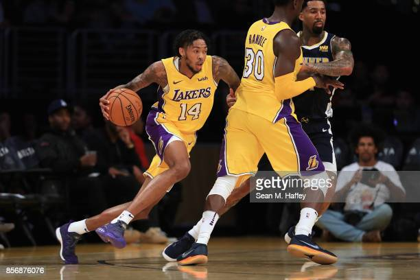 Brandon Ingram dribbles past Julius Randle of the Los Angeles Lakers and Wilson Chandler of the Denver Nuggets during the first half of a preseason...