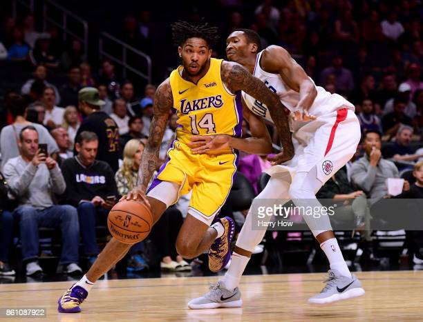 Brandon Ingram of the Los Angeles Lakers drives to the basket on Wesley Johnson of the LA Clippers during the first half at Staples Center on October...