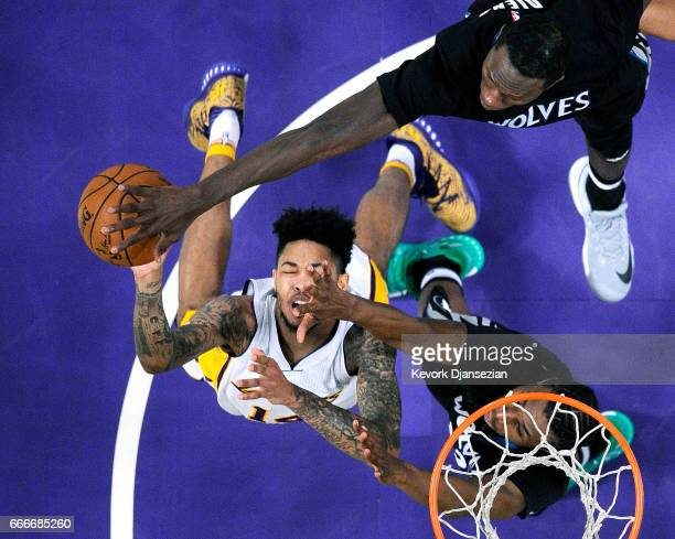 Brandon Ingram of the Los Angeles Lakers goes sup for a layup as he is defended by Andrew Wiggins and Gorgui Dieng of the Minnesota Timberwolves...