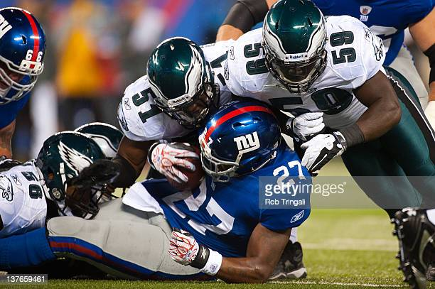 Brandon Jacobs of the New York Giants is tackled during a carry by Trent Cole and Jamar Chaney of the Philadelphia Eagles during the game against the...