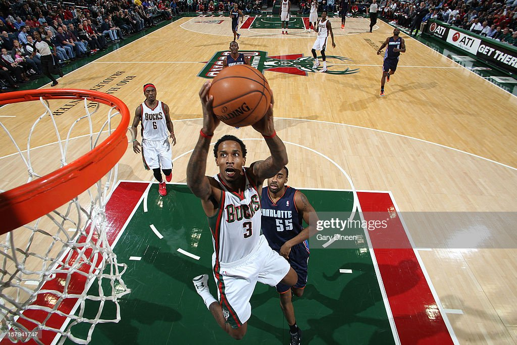 Brandon Jennings #3 of the Milwaukee Bucks goes to the basket against Reggie Williams #55 of the Charlotte Bobcats during the game on December 7, 2012 at the BMO Harris Bradley Center in Milwaukee, Wisconsin.