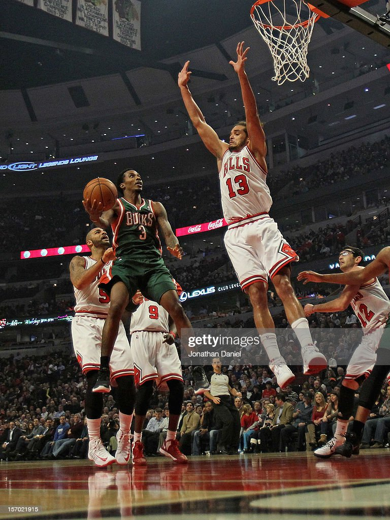 Brandon Jennings #3 of the Milwaukee Bucks leaps to shoot against Joakim Noah #13 of the Chicago Bulls at the United Center on November 26, 2012 in Chicago, Illinois.