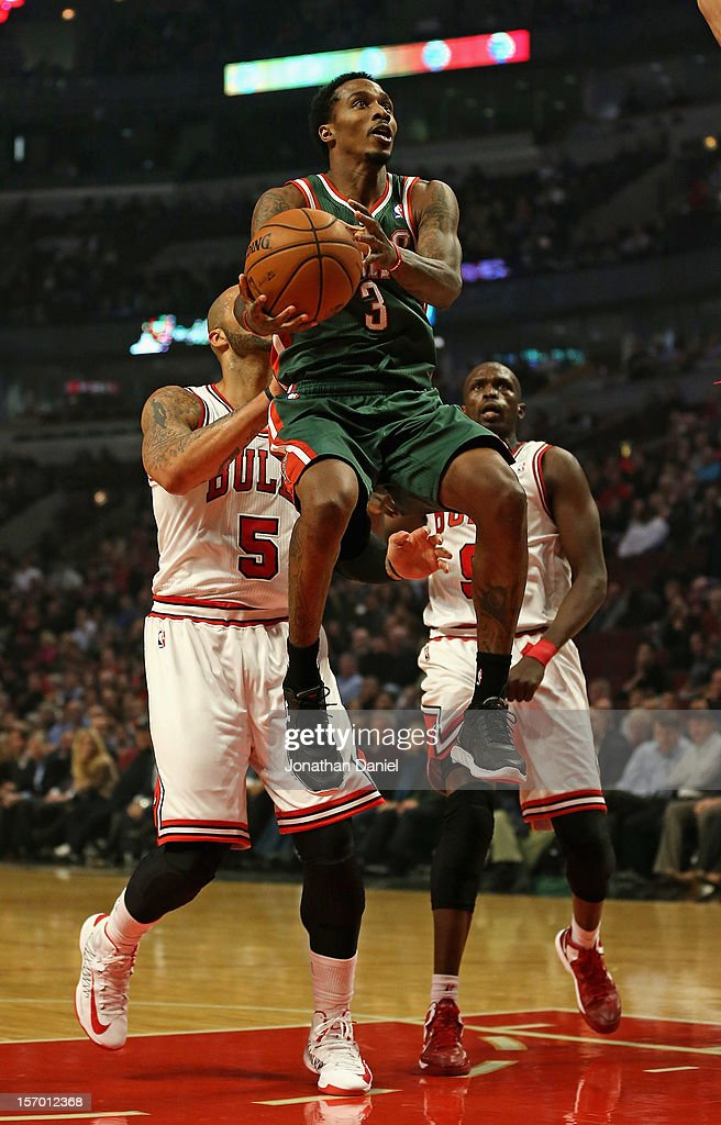 Brandon Jennings #3 of the Milwaukee Bucks leaps to shoot past Carlos Boozer #5 and Loul Deng #9 of the Chicago Bulls at the United Center on November 26, 2012 in Chicago, Illinois.