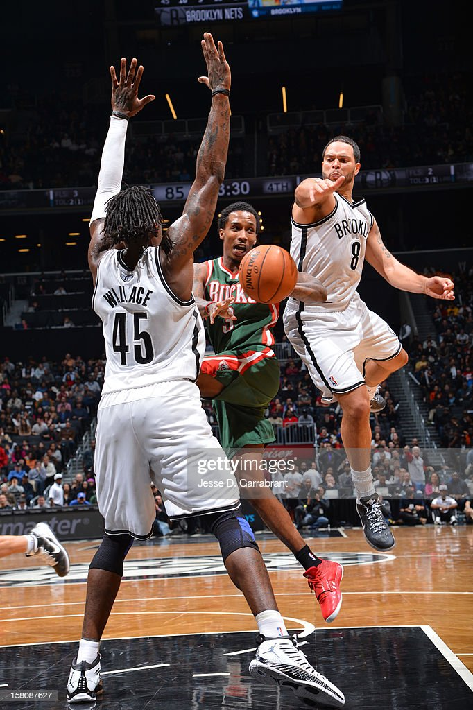 Brandon Jennings #3 of the Milwaukee Bucks makes a pass between <a gi-track='captionPersonalityLinkClicked' href=/galleries/search?phrase=Gerald+Wallace&family=editorial&specificpeople=202117 ng-click='$event.stopPropagation()'>Gerald Wallace</a> #45 and <a gi-track='captionPersonalityLinkClicked' href=/galleries/search?phrase=Deron+Williams&family=editorial&specificpeople=203215 ng-click='$event.stopPropagation()'>Deron Williams</a> #8 of the Brooklyn Nets on December 9, 2012 at the Barclays Center in Brooklyn, New York.