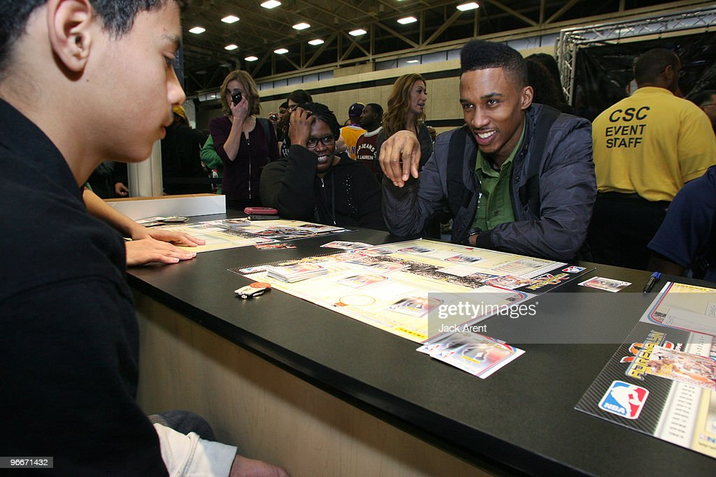 Brandon Jennings of the Milwaukee Bucks plays a trading card game with a fan at the Panini Booth during Jam Session presented by Adidas during All...