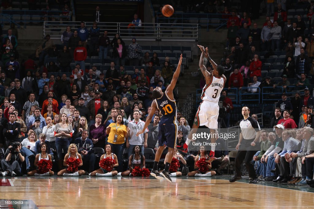 Brandon Jennings #3 of the Milwaukee Bucks shoots a three-pointer against <a gi-track='captionPersonalityLinkClicked' href=/galleries/search?phrase=Alec+Burks&family=editorial&specificpeople=6834208 ng-click='$event.stopPropagation()'>Alec Burks</a> #10 of the Utah Jazz to tie the game with 8.4 seconds remaining in regulation on March 4, 2013 at the BMO Harris Bradley Center in Milwaukee, Wisconsin.