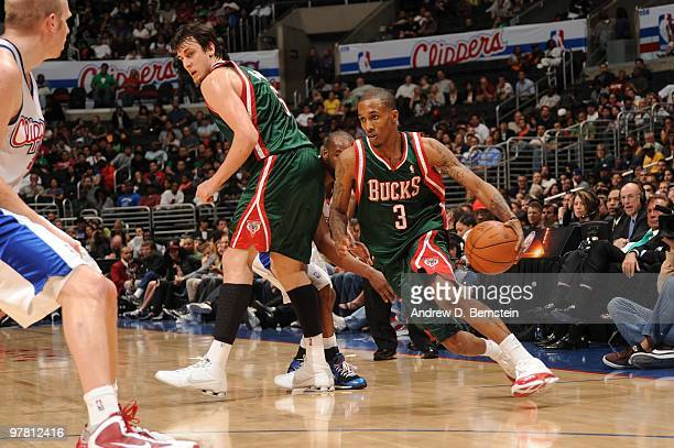 Brandon Jennings of the Milwaukee Bucks uses a screen by teammate Andrew Bogut to drive past Baron Davis of the Los Angeles Clippers during their...