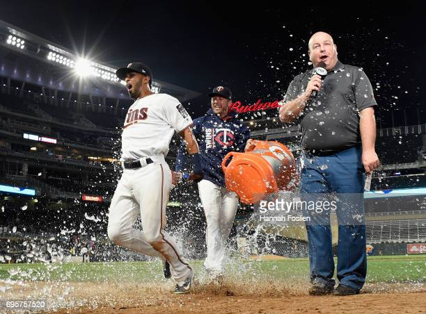 Brandon Kintzler of the Minnesota Twins pours water on teammate Eddie Rosario and Fox Sports North reporter Kevin Gorg after winning the game against...