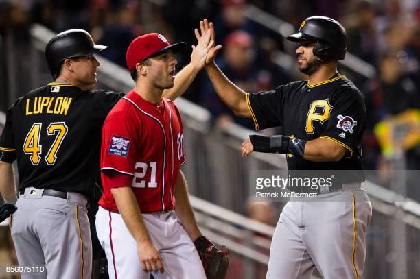 Brandon Kintzler of the Washington Nationals reacts as Jordan Luplow and Elias Diaz of the Pittsburgh Pirates celebrate after scoring on a threerun...