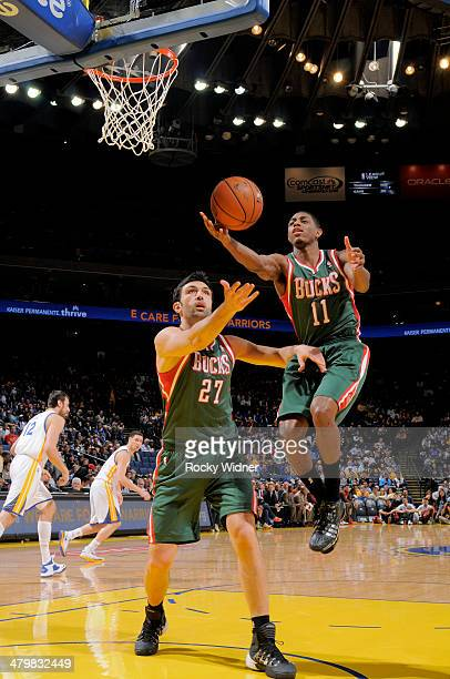 Brandon Knight and Zaza Pachulia of the Milwaukee Bucks rebound against the Golden State Warriors on March 20 2014 at Oracle Arena in Oakland...