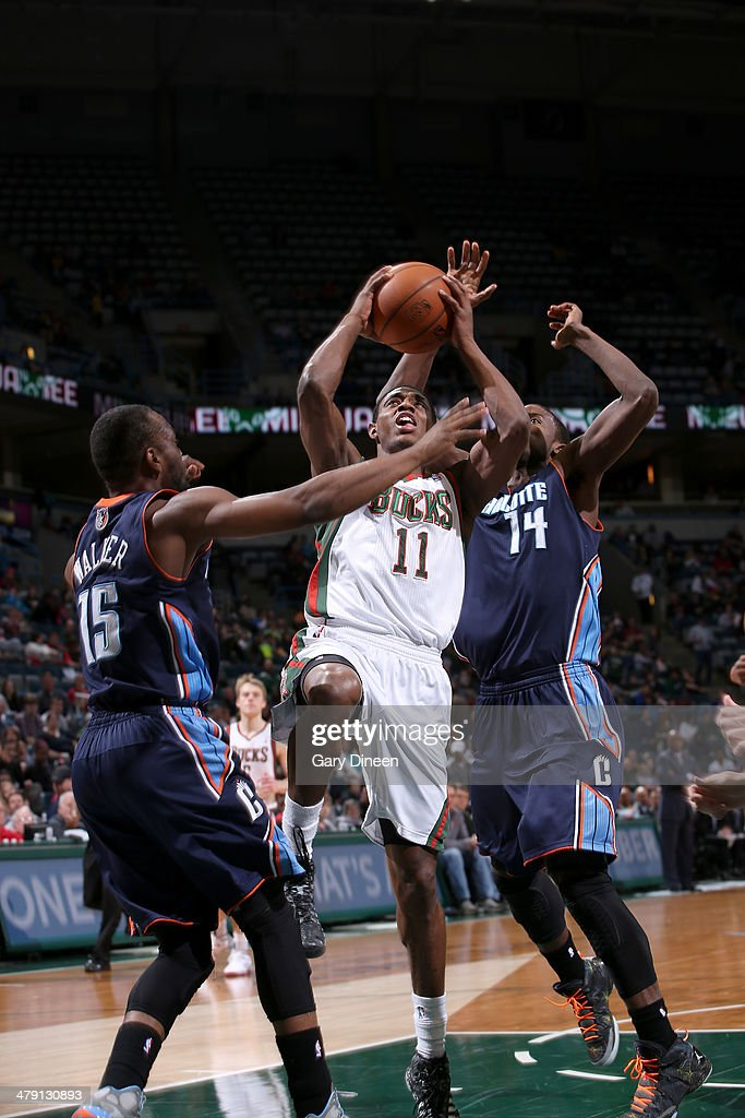 Brandon Knight #11 of the Milwaukee Bucks shoots against (L-R) Kemba Walker #15 and Michael Kidd-Gilchrist #14 of the Charlotte Bobcats on March 16, 2014 at the BMO Harris Bradley Center in Milwaukee, Wisconsin.