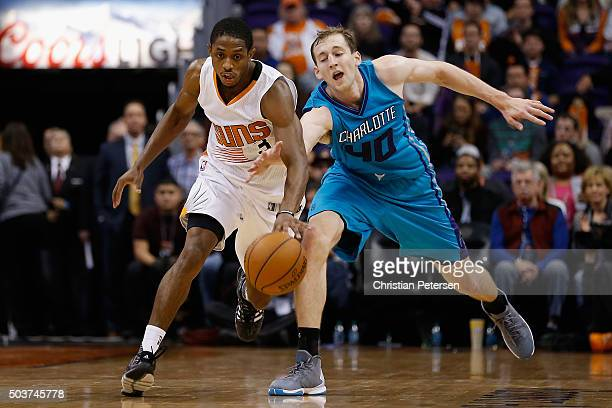 Brandon Knight of the Phoenix Suns and Cody Zeller of the Charlotte Hornets chase a loose ball during the second half of the NBA game at Talking...