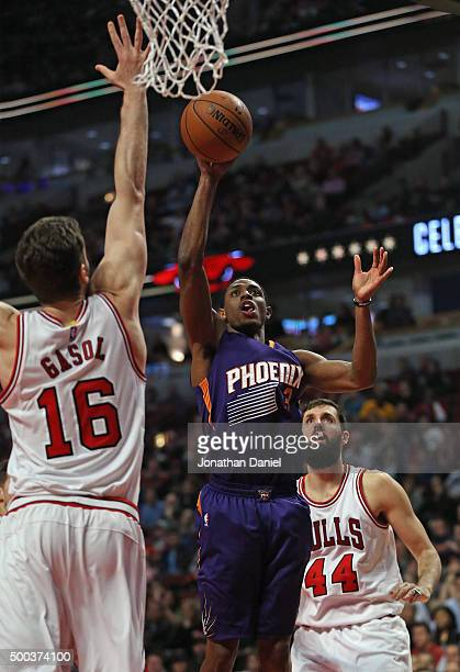 Brandon Knight of the Phoenix Suns puts up a shot between Pau Gasol and Nikola Mirotic of the Chicago Bulls at the United Center on December 7 2015...