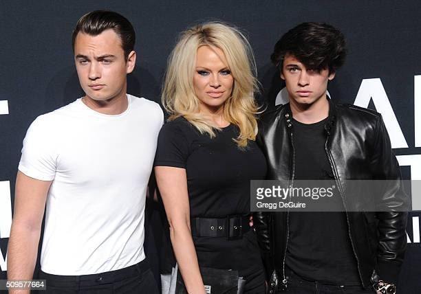 Brandon Lee Pamela Anderson and Dylan Lee attend the Saint Laurent show at The Hollywood Palladium on February 10 2016 in Los Angeles California