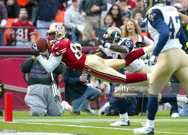 Brandon Lloyd of the San Francisco 49ers catches a touchdown over DeJuan Groce of the St Louis Rams during an NFL game on November 2 2003 at...