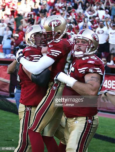 Brandon Lloyd of the San Francisco 49ers celebrates with teammates Brock Gutierrez and Justin Smiley after tying the game with a safety against the...