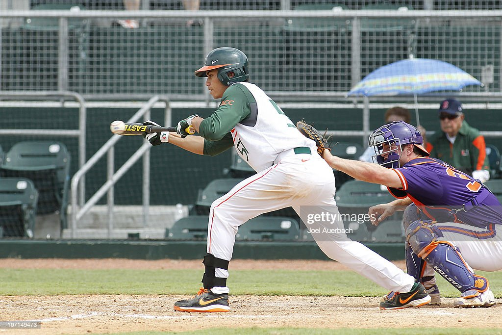 Brandon Lopez #51 of the Miami Hurricanes bunts the ball to load the bases against the Clemson Tigers in the eighth inning on April 21, 2013 at Alex Rodriguez Park at Mark Light Field in Coral Gables, Florida. Miami defeated Clemson 7-0.