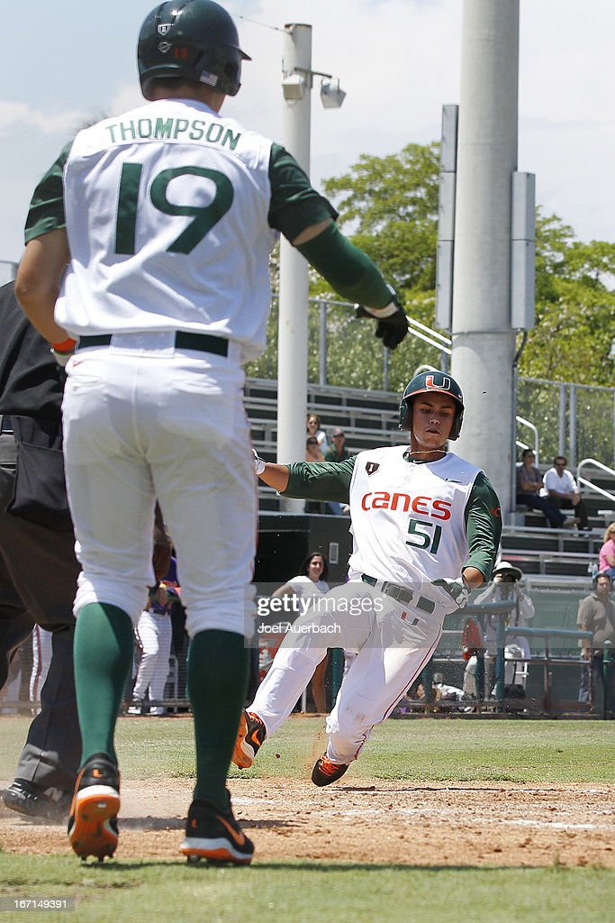 Brandon Lopez #51 scores on a double by Alexander Hernandez #7 (not pictured) of the Miami Hurricanes against the Clemson Tigers on April 21, 2013 at Alex Rodriguez Park at Mark Light Field in Coral Gables, Florida. Miami defeated Clemson 7-0.