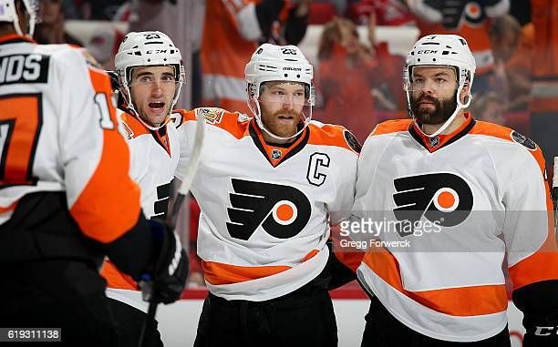 Brandon Manning and Radko Gudas of the Philadephia Flyers congratulate teammate Claude Giroux on his second period goal during an NHL game against...