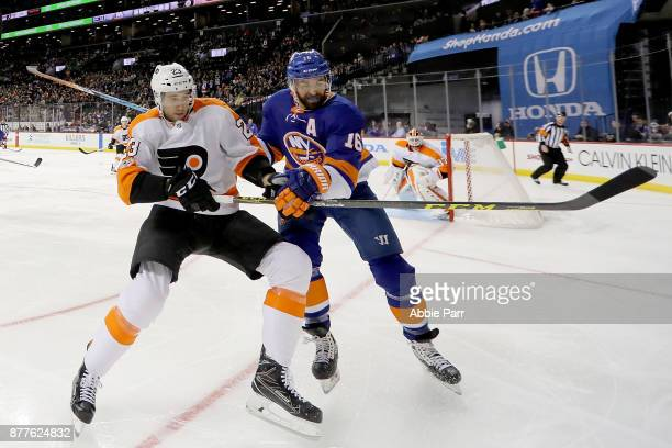 Brandon Manning of the Philadelphia Flyers and Andrew Ladd of the New York Islanders chase after the puck in the second period during their game at...