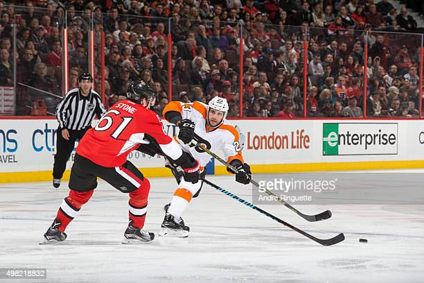Brandon Manning of the Philadelphia Flyers pass the puck against Mark Stone of the Ottawa Senators at Canadian Tire Centre on November 21 2015 in...