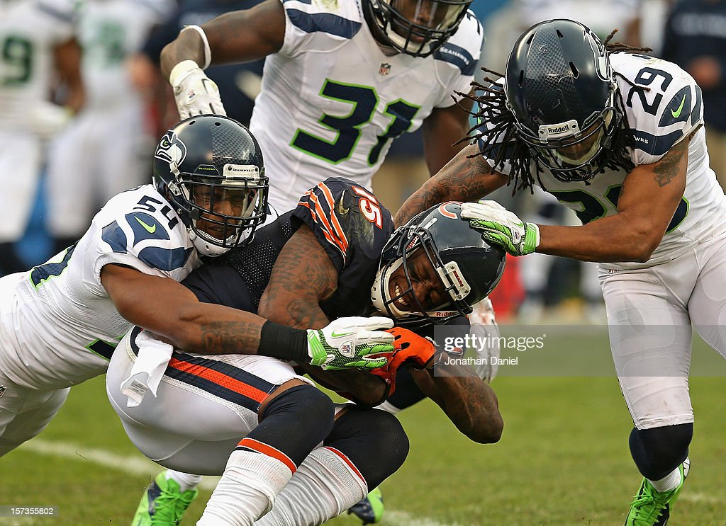 Brandon Marshall #15 of the Chicago Bears is tackled after a catch by Bobby Wagner #54 and Earl Thomas #29 of the Seattle Seahawks at Soldier Field on December 2, 2012 in Chicago, Illinois.