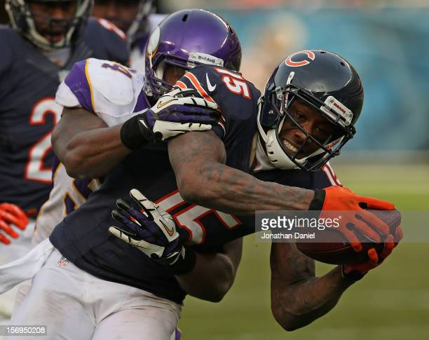 Brandon Marshall of the Chicago Bears is tackled by Jasper Brinkley of the Minnesota Vikings after a catch at Soldier Field on November 25 2012 in...