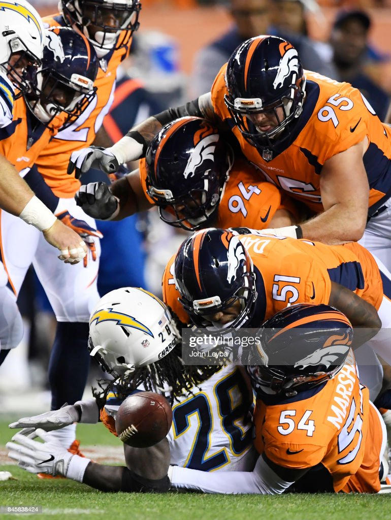 Brandon Marshall (54) of the Denver Broncos forces a fumble on Melvin Gordon (28) of the Los Angeles Chargers as Todd Davis (51) and Derek Wolfe (95) assist during the first quarter on Monday, September 11, 2017. The Denver Broncos hosted the Los Angeles Chargers.