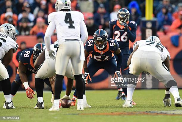 Brandon Marshall of the Denver Broncos keeps his eyes on Derek Carr of the Oakland Raiders as the Raiders get ready to snap the ball in the third...