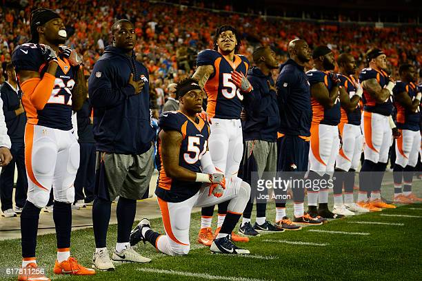 Brandon Marshall of the Denver Broncos kneels as Shane Ray puts his hand on his shoulder for the National Anthem during the first quarter on Monday...
