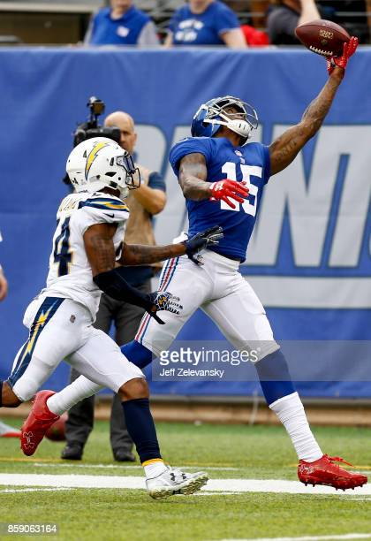 Brandon Marshall of the New York Giants leaps for a pass in front of Trevor Williams of the Los Angeles Chargers before injuring himself on the play...