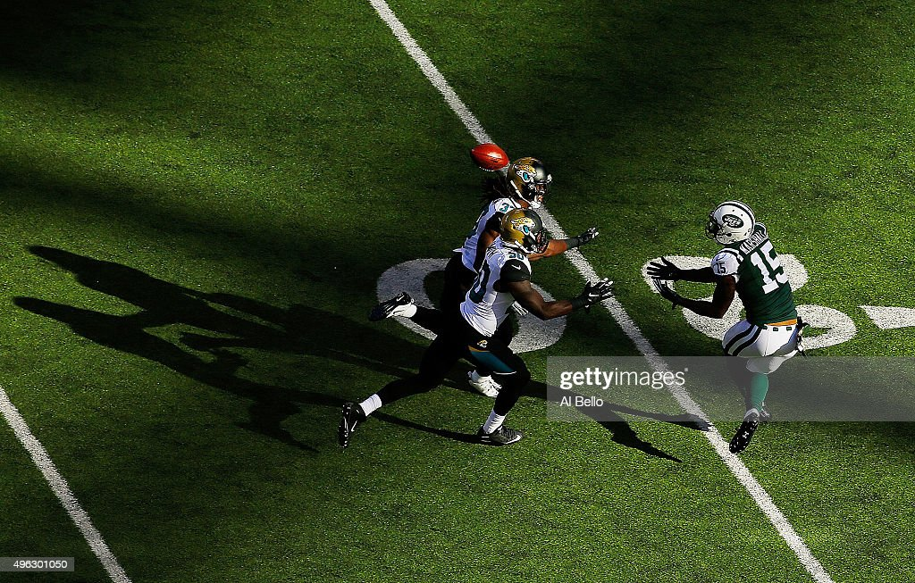 Brandon Marshall #15 of the New York Jets attempts to catch a pass under pressure from Telvin Smith #50 and Johnathan Cyprien #37 of the Jacksonville Jaguars during the second quarter at MetLife Stadium on November 8, 2015 in East Rutherford, New Jersey.