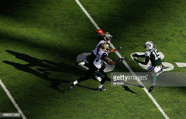 Brandon Marshall of the New York Jets attempts to catch a pass under pressure from Telvin Smith and Johnathan Cyprien of the Jacksonville Jaguars...